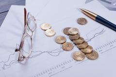说谎在财政图玻璃、笔和疏散硬币 库存照片