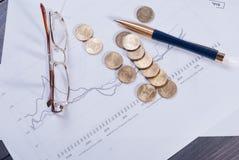 说谎在财政图玻璃、笔和疏散硬币 库存图片
