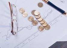 说谎在财政图玻璃、笔和疏散硬币 免版税库存图片