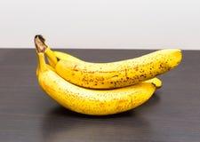 说谎在黑暗的木桌上的束香蕉 图库摄影