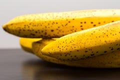 说谎在黑暗的木桌上的束香蕉 库存照片