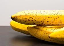 说谎在黑暗的木桌上的束香蕉 库存图片