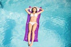 说谎在水池的气垫上的白色比基尼泳装的妇女 免版税库存照片