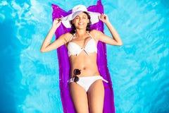 说谎在水池的气垫上的白色比基尼泳装的妇女 库存图片
