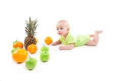 说谎在他的在果子和看中的胃的逗人喜爱的微笑的婴孩 免版税图库摄影