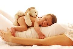 说谎在他的妈妈的一个逗人喜爱的矮小的新出生的婴孩 免版税库存照片