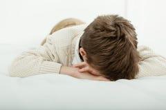 说谎在他的床上的年轻男孩睡觉或哭泣 免版税库存照片