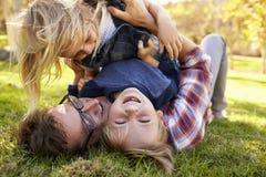 说谎在他们的爸爸顶部的两个小孩在公园 库存图片