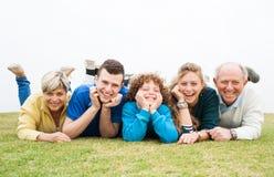 说谎在绿色草坪的愉快的家庭 免版税库存照片
