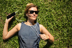 说谎在绿草和听的音乐的少妇 图库摄影