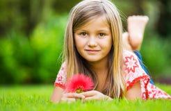 说谎在绿草的一个微笑的小女孩的画象 图库摄影