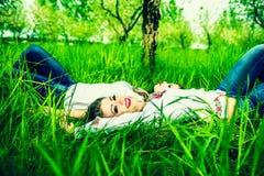 说谎在绿草的两个愉快的俏丽的女孩 库存图片