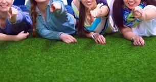 说谎在绿草的四个少妇 免版税库存图片
