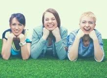说谎在绿草的四个少妇 免版税库存照片