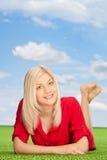 说谎在绿草的妇女调遣户外 免版税库存图片