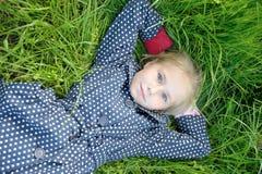 说谎在绿草的小女孩画象 库存图片