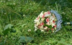 说谎在绿草的桃红色和白玫瑰婚礼花束  免版税图库摄影