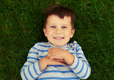 说谎在绿草的激动的小男孩 库存图片