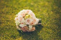 说谎在绿草的白色婚礼花束 免版税库存照片