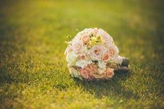 说谎在绿草的白色婚礼花束 免版税库存图片