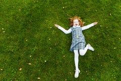 说谎在绿草的红头发人女孩在公园 库存图片
