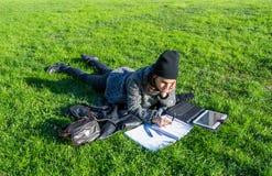 说谎在绿草的逗人喜爱的女孩学习与片剂和笔记本 库存图片