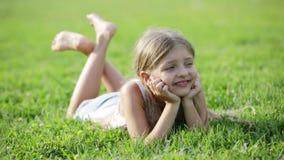 说谎在绿草的高兴的小女孩在公园 股票视频