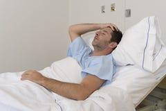 说谎在医院病床的年轻耐心人休息疲倦的看起来哀伤和沮丧担心 免版税库存照片