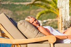 说谎在deckchair的白肤金发的妇女,享受暑假 库存图片