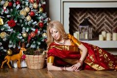 说谎在Th的印度红莎丽服的美丽和肉欲的白肤金发的女孩 库存图片