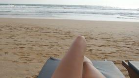 说谎少妇的观点通过海和晒黑sunbed 在享用的躺椅的女性腿放松和 股票录像