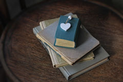 说谎木表面上的旧书和心脏 免版税库存图片