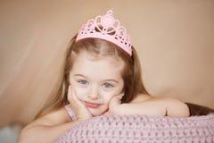 说谎桃红色的礼服的美丽的公主女孩下来乏味 库存图片