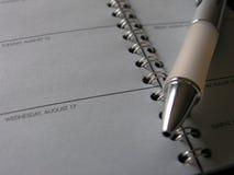 说谎横跨天定时器开放页的笔  免版税库存照片