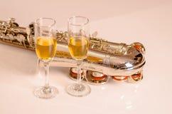 说谎白色表面、音符纸和两杯上的发光的萨克斯管香槟坐在它旁边 图库摄影