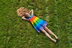 说谎的女孩在新近地被割的草坪 免版税库存照片