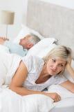 说谎除人以外的被拉紧的妇女在床上 免版税库存照片