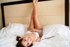 说谎颠倒与腿的妇女反对床头板 库存图片