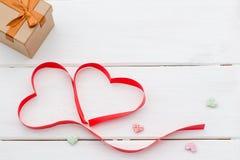 说谎以两个心脏和礼物盒的形式红色丝带 免版税库存照片