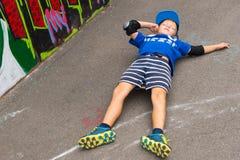 说谎年轻的男孩在全部支持在街道画墙壁附近 库存图片