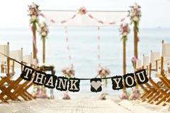 谢谢措辞横幅在美丽的海滩婚礼设定椅子 免版税库存图片