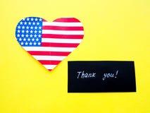 谢谢签字在有美国国旗的一个黑板在黄色背景,美国 库存照片