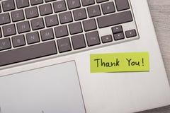 谢谢!关于膝上型计算机的稠粘的笔记 免版税库存照片