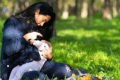 谨慎地哺乳她的婴孩的一个爱恋的母亲在豪华的城市公园 免版税库存图片