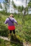 谨慎妇女设法在佩带衣物的错误的类型活动的原野步行 图库摄影