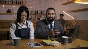 谴责雇员的严密的经理在咖啡馆 影视素材