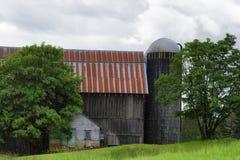 谷仓和筒仓在一个山坡在多云天空下 免版税图库摄影
