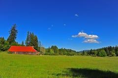 谷仓明亮的草甸老红色屋顶 免版税图库摄影