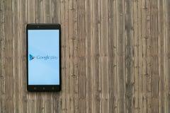 谷歌在智能手机屏幕上的戏剧商标在木背景 库存图片
