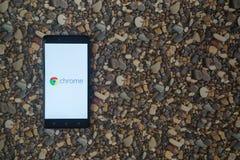 谷歌在智能手机的镀铬物商标在小石头背景  免版税库存照片